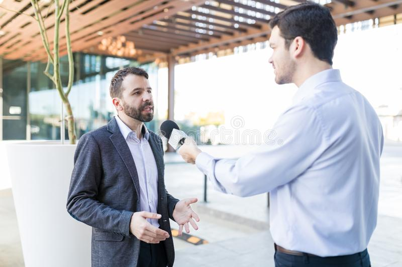 Reporter With Microphone Interviewing Professional. Mid adult famous personality wearing suit and giving interview to broadcaster outdoors stock photography