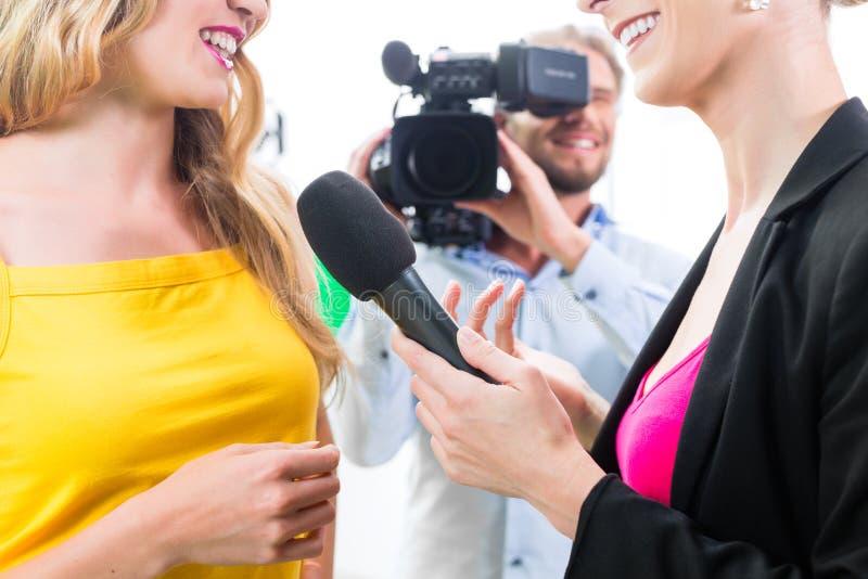 Reporter och kameraman skjuter en intervju royaltyfri foto
