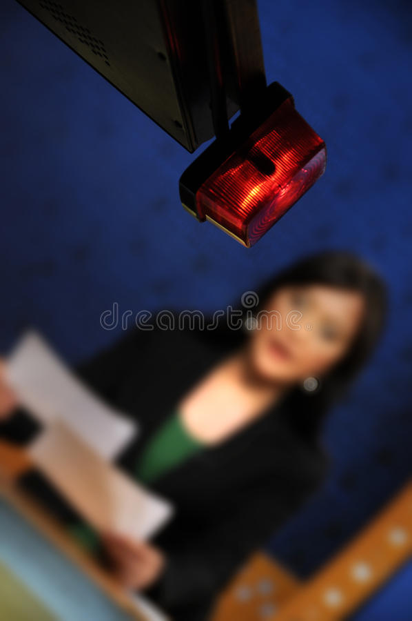 Reporter presenting news in TV studio. On the air sign stock image