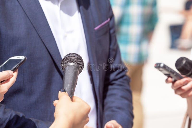 Reporter som gör intervju med businesspersonen, politikern eller talesmannen royaltyfri bild