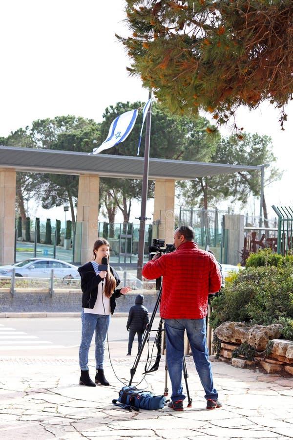 Reporter teenager della ragazza di età che parla davanti al knesst fotografia stock libera da diritti