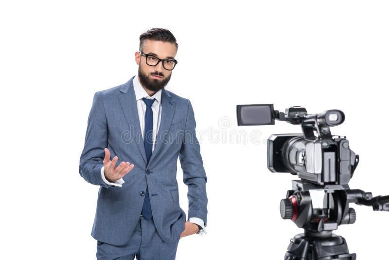 reporter telewizyjny gestykuluje i stoi przed kamerą, obraz stock