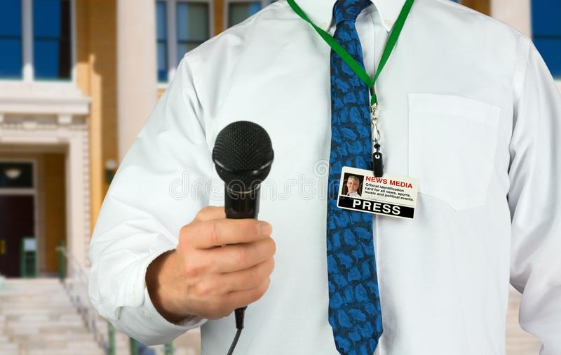 Reporter telewizyjny z mikrofonu i prasowej przepustki środków przekazu kartą identyfikacyjna obrazy stock