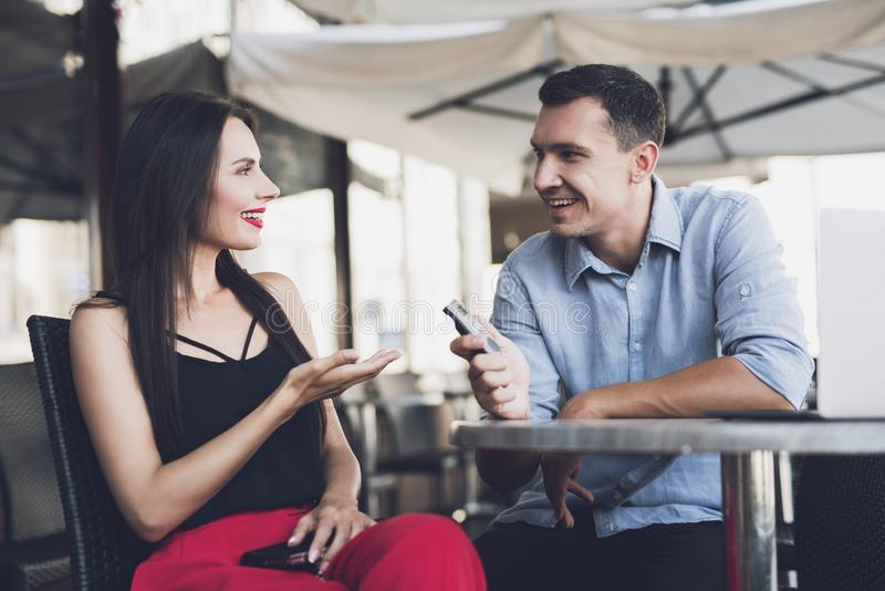 A journalist talking with a beautiful girl. A reporter at work. The journalist writes down the answers of the girl to the dictophone. At the table there is a royalty free stock photos