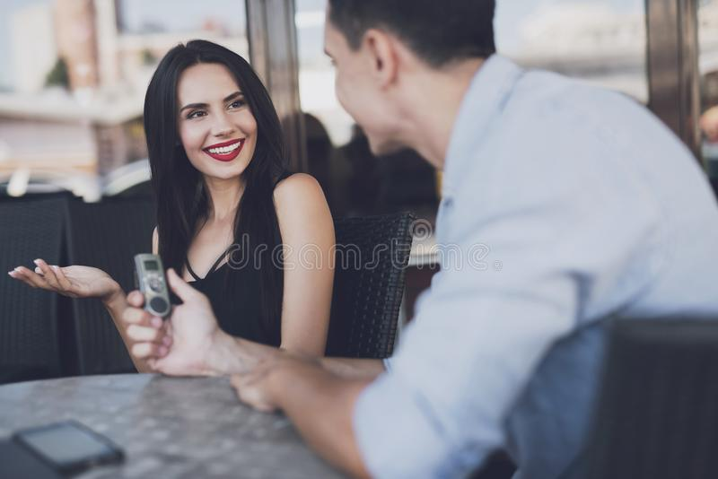 The girl coquettishly answers questions. A reporter at work. The women answers questions with pleasure. The men writes down all the answers to the dictophone stock images