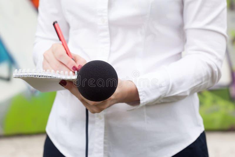 Reportero de sexo femenino o periodista en la rueda de prensa, escribiendo notas fotografía de archivo