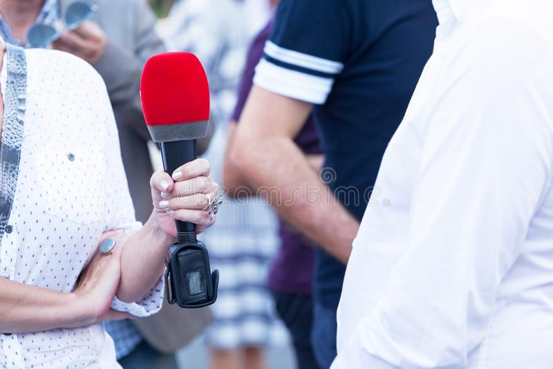 Reportero de sexo femenino que hace la prensa o la entrevista de los medios fotos de archivo libres de regalías