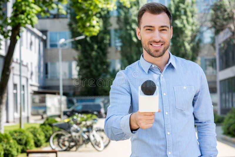 reportero de sexo masculino sonriente de las noticias que toma entrevista con el micrófono fotografía de archivo