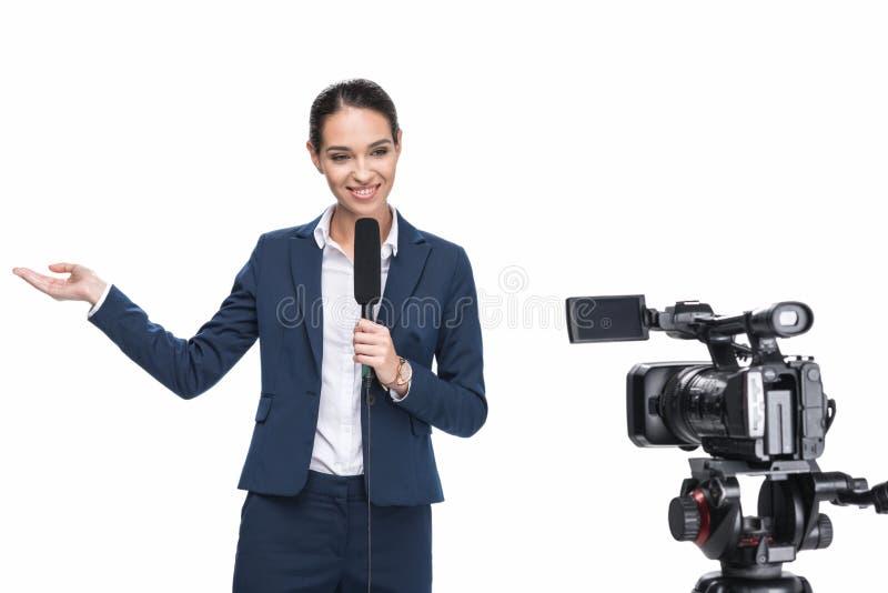 reportero de televisión de sexo femenino sonriente hermoso con el micrófono que mira la cámara, fotografía de archivo