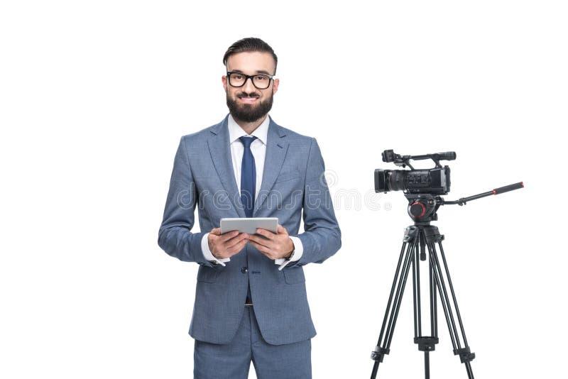 reportero de televisión de sexo masculino que usa la tableta digital que se coloca cerca de la cámara de vídeo, foto de archivo