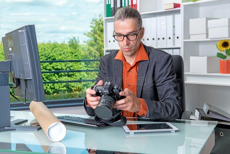 Reportero que trabaja en redacción con el ordenador y la cámara fotografía de archivo libre de regalías