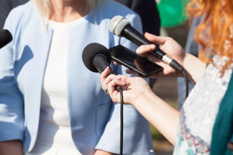 Reporteros que hacen entrevista de los medios con la mujer de negocios o p femenino foto de archivo