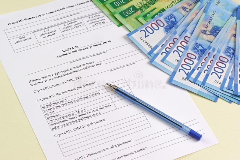 Reporting form in Russian `Map of special assessment of working conditions`. Payment and summarizing the work of the special assessment Commission. Pen and royalty free stock images