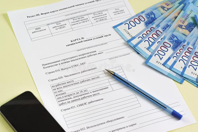 Reporting form in Russian `Map of special assessment of working conditions`. Summing up the work of the Commission on special procedures. Pen, money and royalty free stock photography