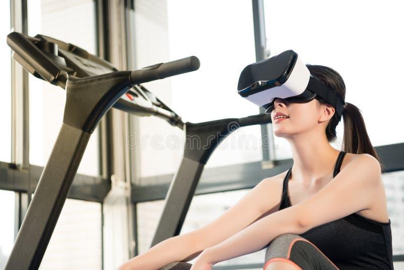 Repos asiatique de femme de beauté sur le tapis roulant avec le casque de VR photos libres de droits