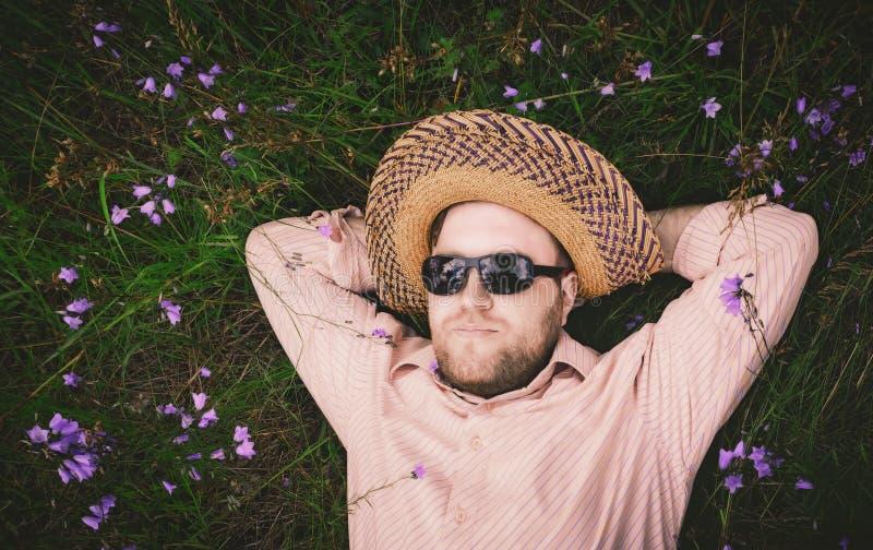 Repos d'homme sur l'herbe et les campanules images libres de droits