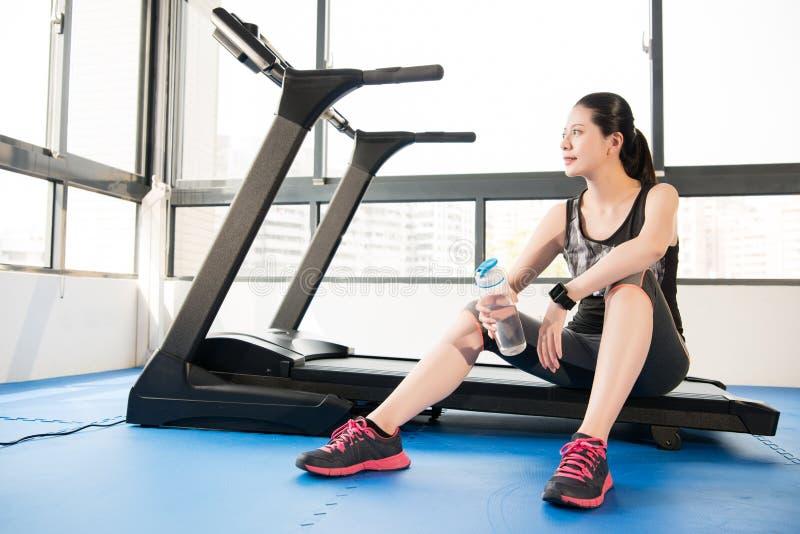 Repos de femme de sport sur l'eau potable de smartwatch d'utilisation de tapis roulant photographie stock