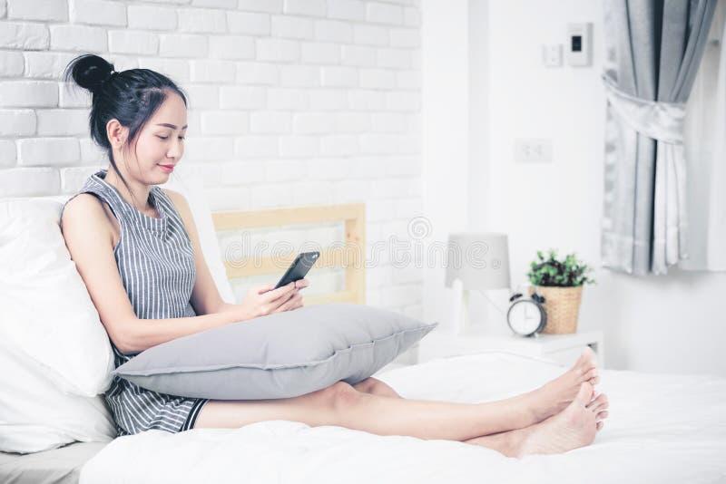 Repos de femme et détente sur le lit utilisant des dispositifs de téléphone portable images stock