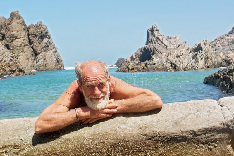 Repos heureux de vieil homme sur la plage images libres de droits