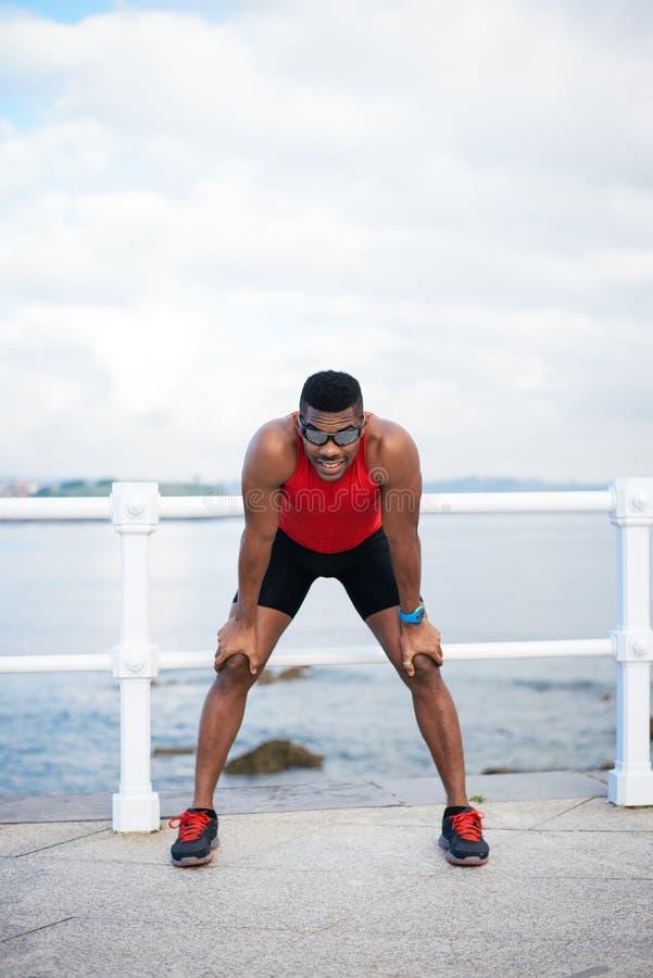 Repos masculin noir motivé de coureur image stock