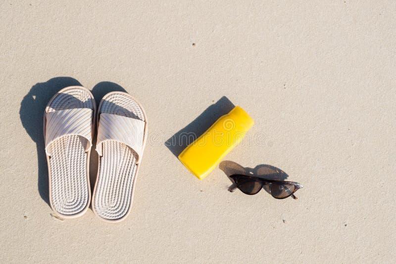 Repos sur la plage : pantoufles, crème protectrice et lunettes de soleil sur le sable propre images libres de droits