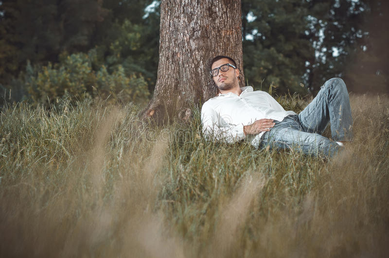 Repose. Young handsome man repose on grass against a tree. Gorgeous guy lie down on meadow in nature. Outdoors - outside stock photo