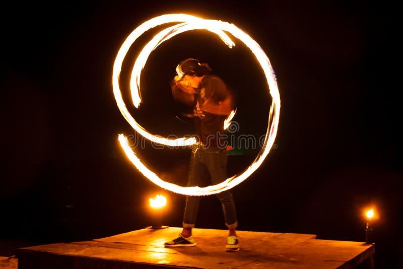 Représentation de jonglerie du feu d'artiste de rue La peinture légère et la longue photo d'exposition à la forme traîne Île de p photo stock