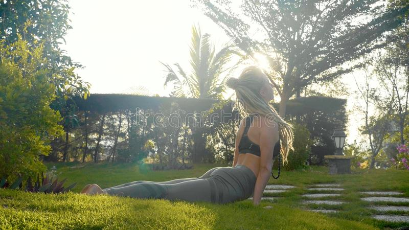 Représentation professionnelle de yoga d'asana par une jeune fille à l'arrière-cour de sa maison images stock