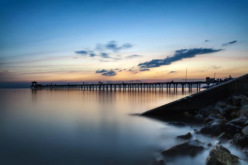 Represa escura da rocha no oceano azul no por do sol crepuscular e na ponte de madeira imagem de stock royalty free