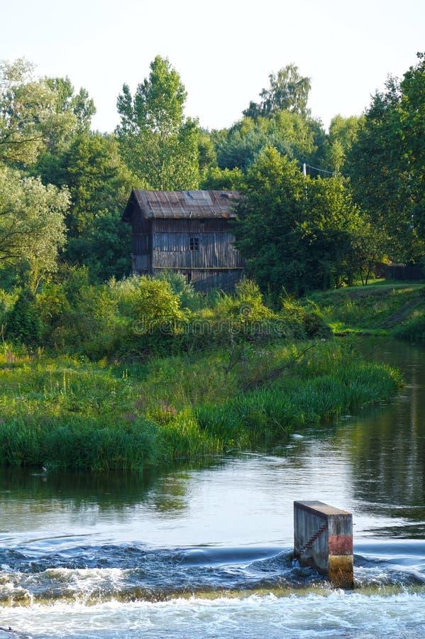 Represa no rio no fundo um moinho de água histórico, de madeira imagens de stock
