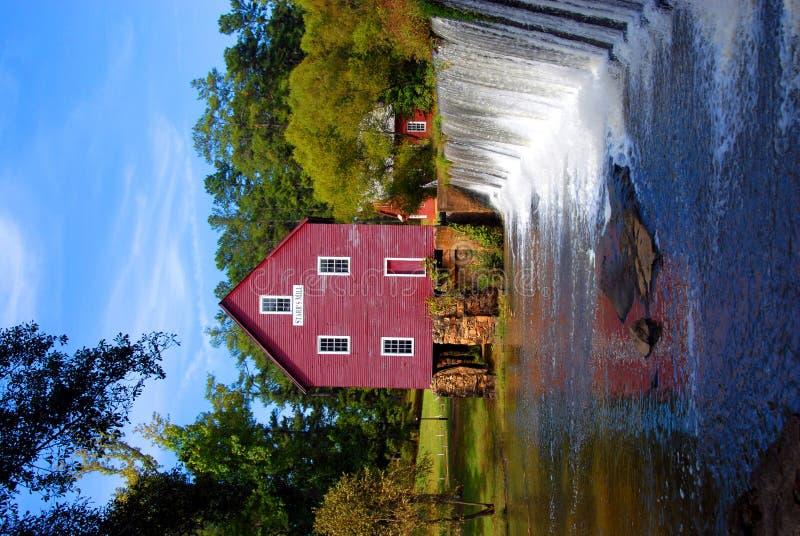 Represa vermelha velha do moinho e do rio fotos de stock