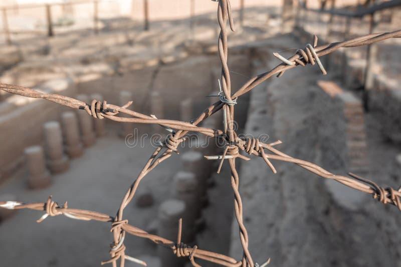 Representó confuso columnas de un templo excavado cerca de Kerma en Sudán detrás del alambre de púas agudamente enfocado, África foto de archivo
