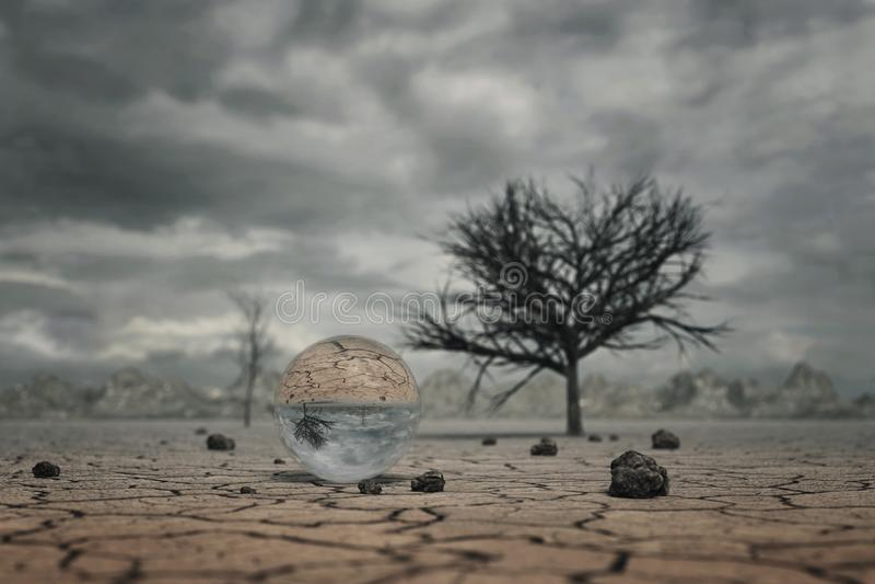 representación 3d de la bola de cristal en el paisaje del suelo seco con los árboles fotografía de archivo