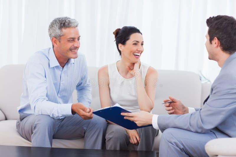 Representant och klienter som tillsammans talar och skrattar på soffan royaltyfri bild