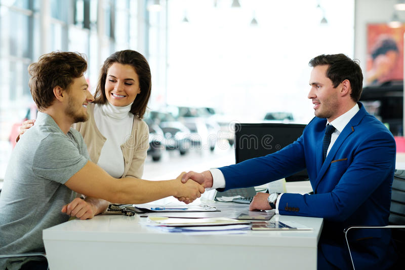 Representant och kund som skakar händer som gratulerar sig på återförsäljarevisningslokalen fotografering för bildbyråer