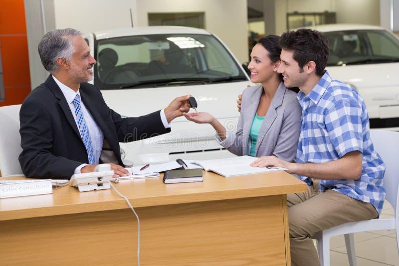 Representant som ger biltangenter till ett par royaltyfri foto