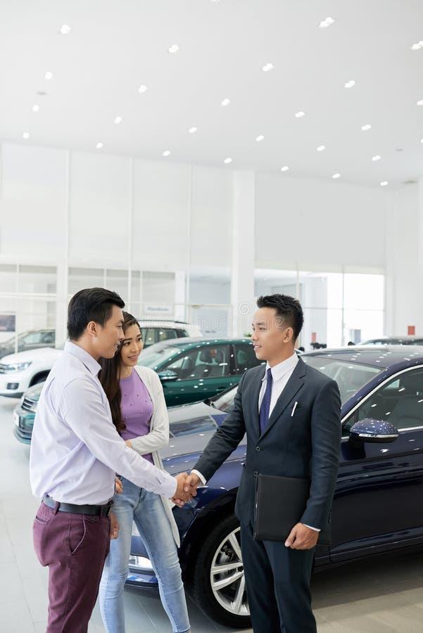 Representant som möter klienter i bilåterförsäljare royaltyfria bilder