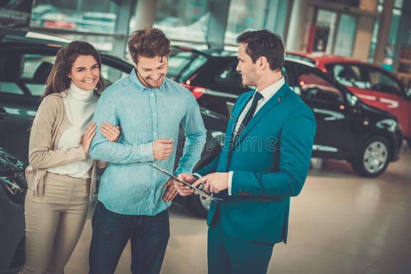 Representant som talar till ett ungt par på återförsäljarevisningslokalen arkivfoton