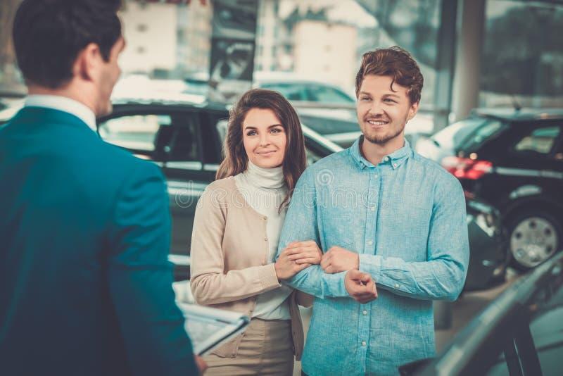 Representant som talar till ett ungt par på återförsäljarevisningslokalen fotografering för bildbyråer