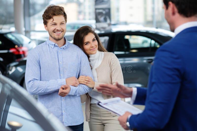 Representant som talar till ett ungt par på återförsäljarevisningslokalen arkivfoto