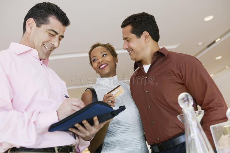 RepresentantCalculating Bill While Couple Holding Credit kort i lager arkivbilder
