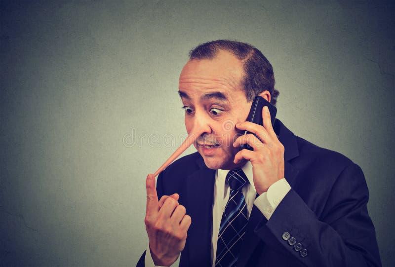 Representante de serviço ao cliente do mentiroso Homem com nariz longo que fala no encontro do telefone celular imagens de stock royalty free
