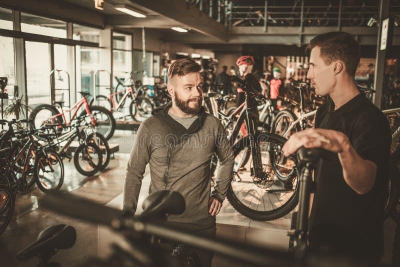 Representanten som visar en ny cykel till den intresserade kunden i cykel, shoppar arkivbild