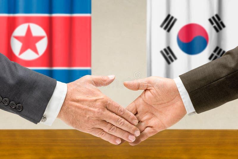 Representanter av Nordkorea och Sydkorea skakar händer royaltyfria foton