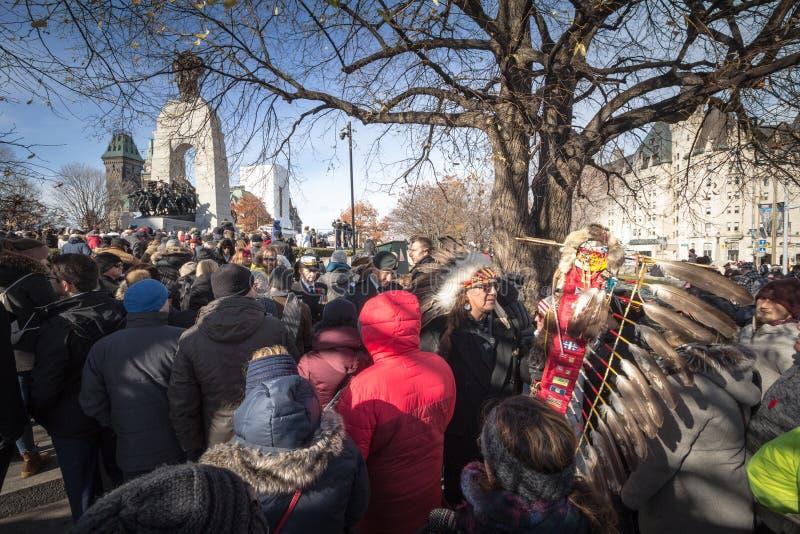 Representantes de las primeras naciones indígenas con su tocado tradicional en frente el monumento de guerra nacional de Ottawa foto de archivo