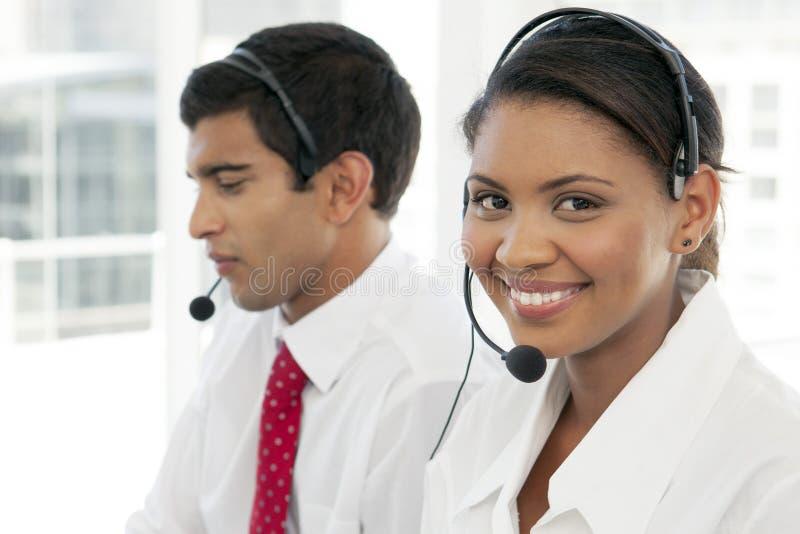 Representantes/delegados de servicio de atención al cliente en el trabajo en centro de atención telefónica multiétnico foto de archivo libre de regalías