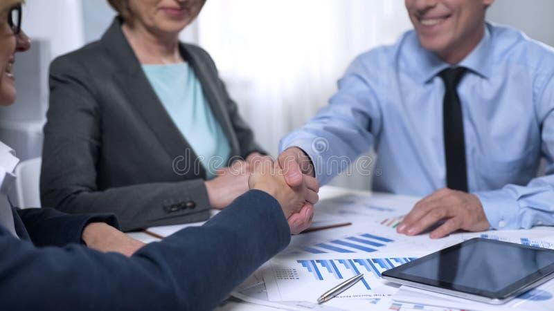 Representantes masculinos de la compañía de las señoras de la reunión del inversor, discutiendo el contrato fotografía de archivo libre de regalías