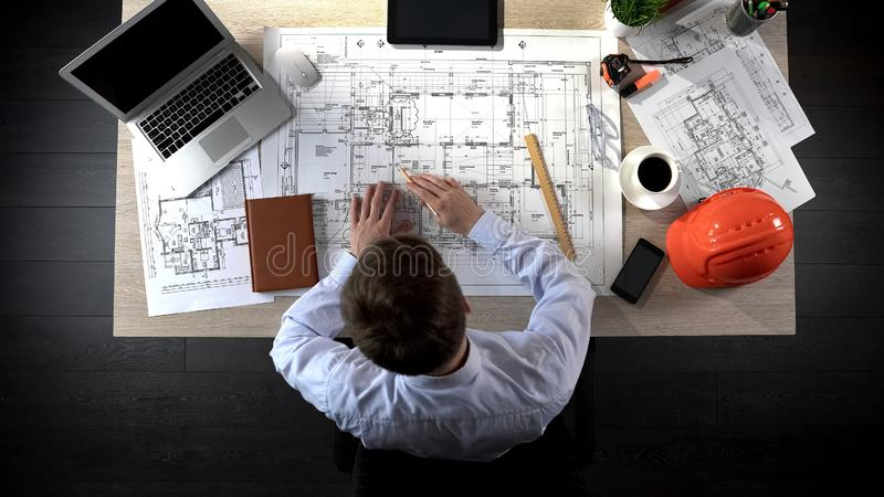 Representative of construction company preparing drawing of office building royalty free stock image