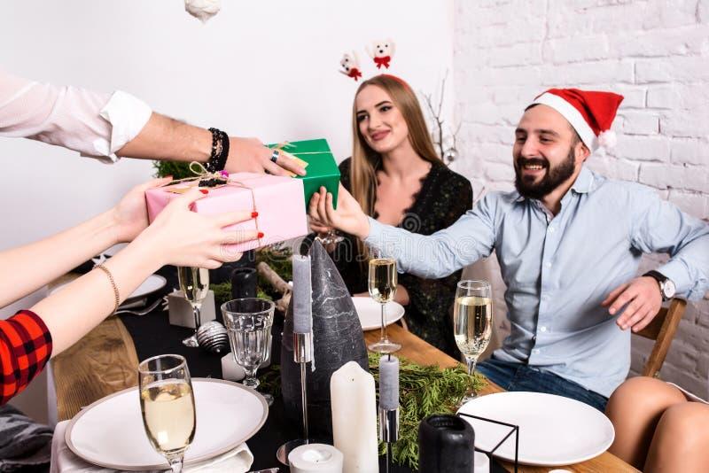Represente mostrar al grupo de amigos que celebran la Navidad en casa y que dan presentes el uno al otro foto de archivo