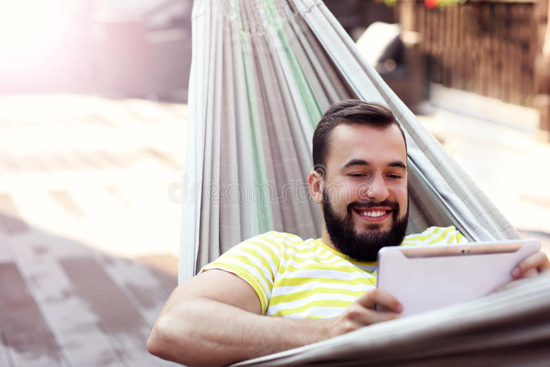 Represente mostrar al hombre feliz que descansa sobre la hamaca con la tableta imagen de archivo libre de regalías